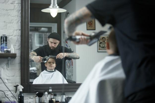 Kinderfriseur, der kleinen jungen vor einem dunklen hintergrund schneidet. zufriedener süßer vorschuljunge, der den haarschnitt bekommt.