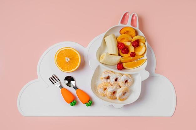 Kinderfrühstück. niedlicher teller in form eines hasen mit donuts und früchten. essensidee für kinder.