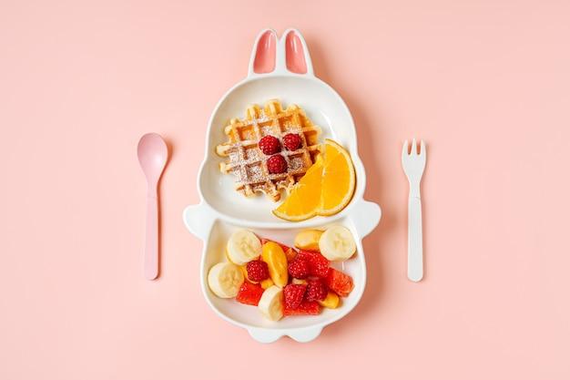 Kinderfrühstück. niedlicher teller in form eines hasen mit waffeln und früchten. essensidee für kinder.