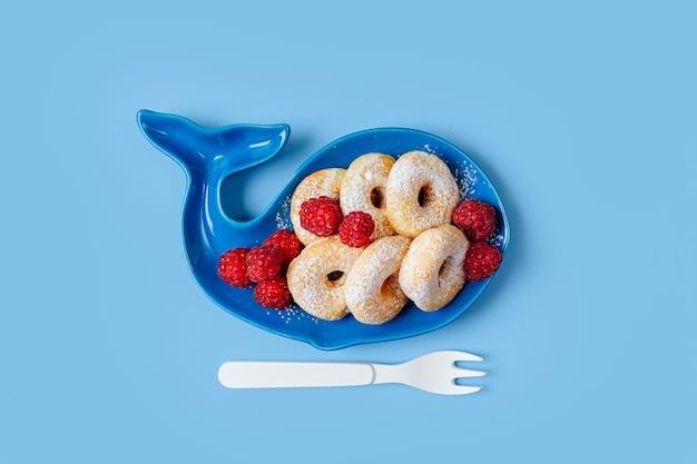 Kinderfrühstück. teller in form eines wals mit donuts und beeren. essensidee für kinder.