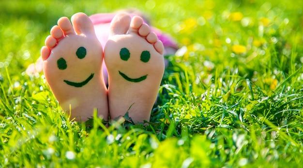 Kinderfüße auf dem gras, die ein lächeln zeichnen