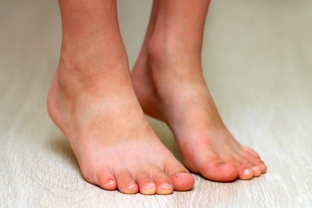 Kinderfüße auf parkett lamellenförmig angeordneter hölzerner beschaffenheitsbodennahaufnahme. gesundheitswesen-konzept
