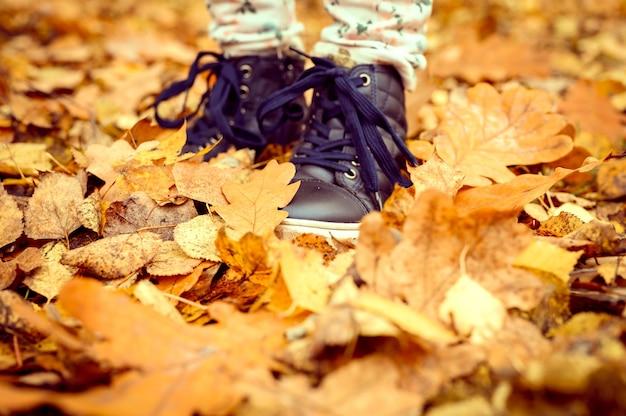 Kinderfüße in schuhen in einem haufen gefallener orangenblätter im herbst in einem herbstwald oder park. kinder gehen oder reisen in der natur