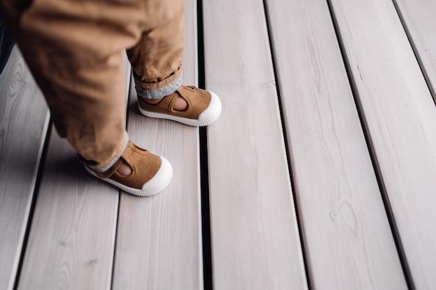 Kinderfüße in stiefeln, die auf weißer oberfläche wie holzdeck stehen