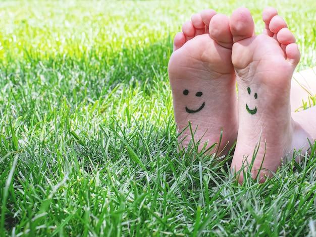 Kinderfüße mit einem farbmuster lächeln auf dem grünen gras. selektiver fokus. natur.