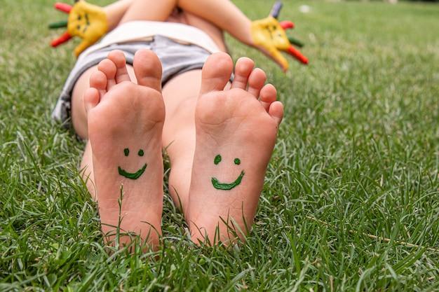Kinderfüße mit einem farbmuster lächeln auf dem grünen gras. selektiver fokus.