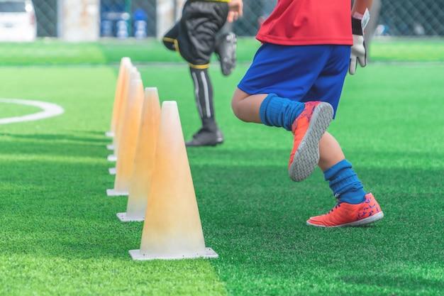 Kinderfüße mit fußballschuhen auf trainingskegel