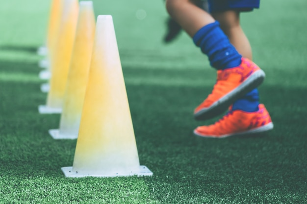 Kinderfüße mit fußballschuhen, die auf trainingskegel auf fußballplatz trainieren