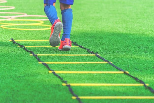 Kinderfüße mit fußballstiefeln ausbildend auf beweglichkeitsgeschwindigkeitsleiter im fußballtraining.