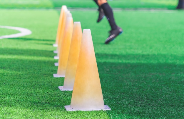 Kinderfüße mit fußballstiefeln ausbildend auf trainingskegel auf fußballplatz