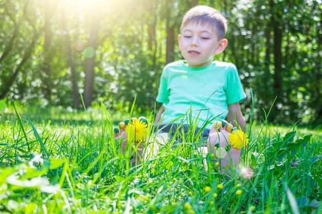 Kinderfüße mit löwenzahnblume auf grünem gras am sonnigen sommertag
