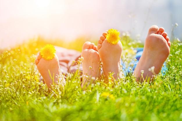 Kinderfüße mit löwenzahnblumen, die auf grünem gras am sonnigen tag liegen. konzept glücklich chidlhood.