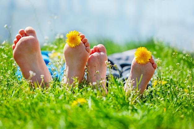 Kinderfüße mit löwenzahnblumen, die auf grünem gras am sonnigen tag liegen. konzept glückliche kindheit.
