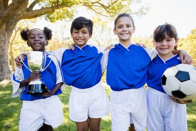 Kinderfußballteam im rohen lächeln