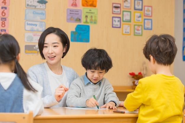 Kindergärtnerin spielt mit kindern