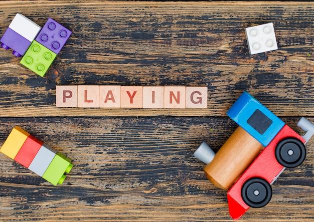 Kindergartenkonzept mit holzwürfeln, kinderspielzeug auf hölzernem hintergrund flach legen.