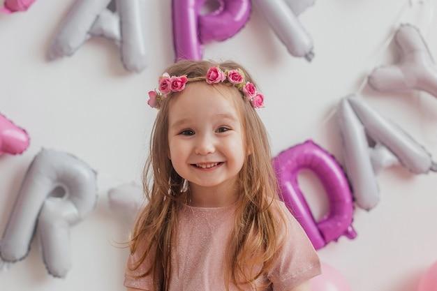 Kindergeburtstag. porträt eines niedlichen kleinen mädchens in einem rosa kleid, das vor der kamera aufwirft. Premium Fotos