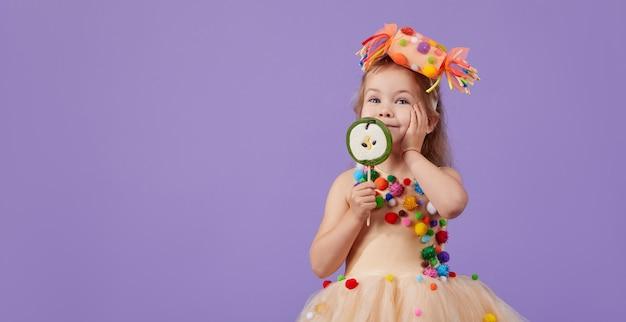 Kindergeburtstagsfeier, maskerade. kleines glückliches kleinkindkindmädchen in einem geschwollenen tutu-kostüm, das spaß auf violettem raum hat. platz für text