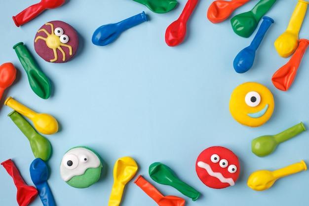 Kindergeburtstagshalloween-partyhintergrund, rahmen mit bonbons und ballone auf blauer oberfläche
