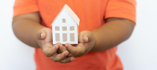 Kindergestenhand, die hausmodell für familienversicherung und darlehenshypothekenkonzept hält