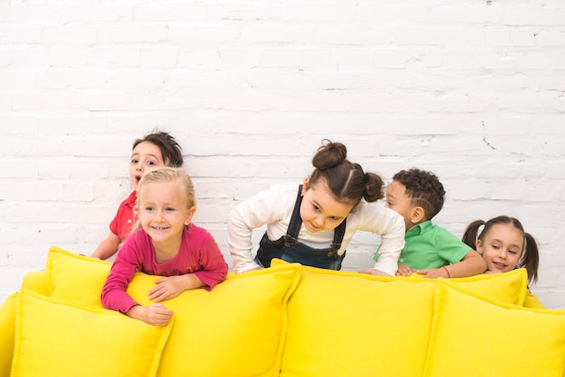 Kindergruppe, die in einem sofa spielt