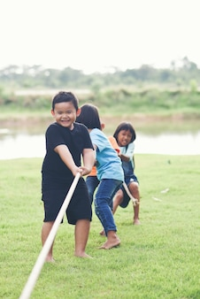 Kindergruppe, die tauziehen am park spielt