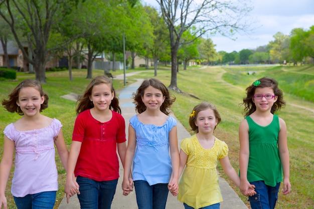 Kindergruppe schwestermädchen und -freunde, die in park gehen