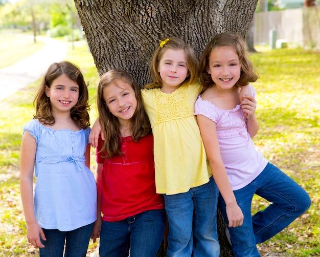 Kindergruppenfreundmädchen, die auf baum spielen