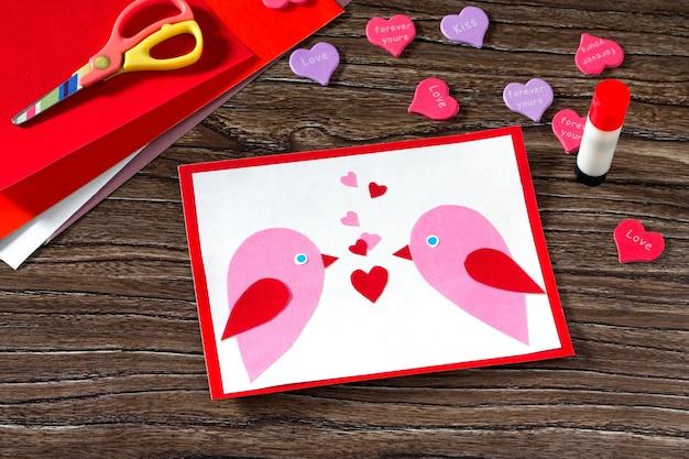 Kindergrußkarte zwei vögel und herz aus einer zeitung am valentinstag.