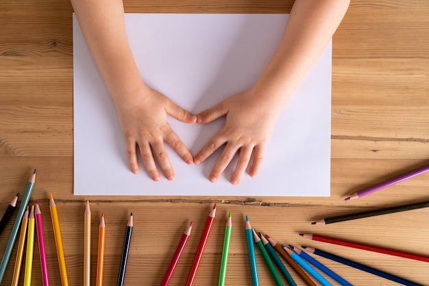 Kinderhände auf dem tisch und ein weißes blatt papier und buntstifte, das konzept von