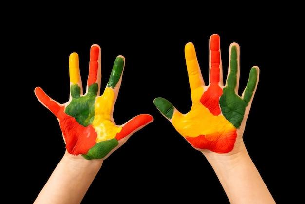 Kinderhände auf einem mit farbiger farbe schwarz gefärbten.