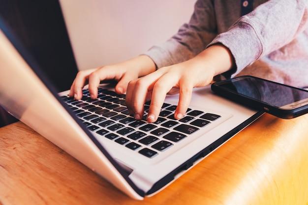 Kinderhände auf laptop-computer tastatur nahe bei einem handy, zum des geschäfts zu tätigen.