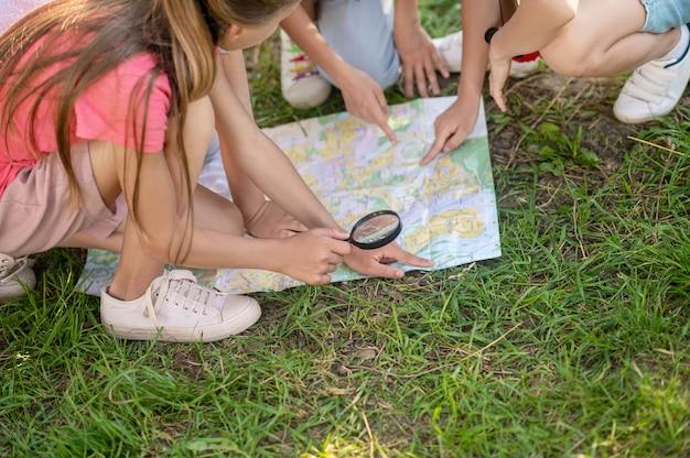Kinderhände, die auf die karte auf dem rasen zeigen