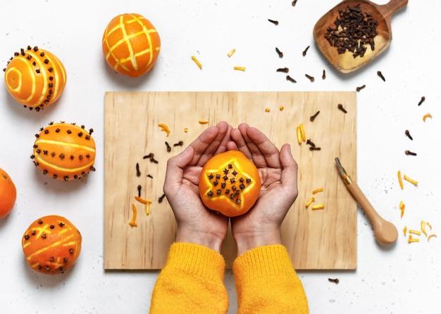 Kinderhände, die einen orangefarbenen pomanderball der nelke mit sternmotiv, draufsicht halten