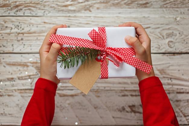 Kinderhände, die geschenk-weihnachtsbox halten. ansicht von oben.
