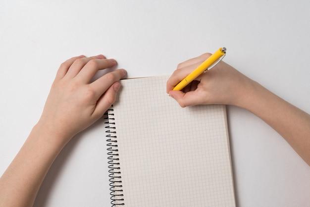 Kinderhände, die in notizbuch schreiben. kind hausaufgaben machen. ansicht von oben