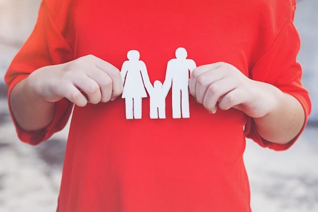 Kinderhände, die kleine vorbildliche familie halten