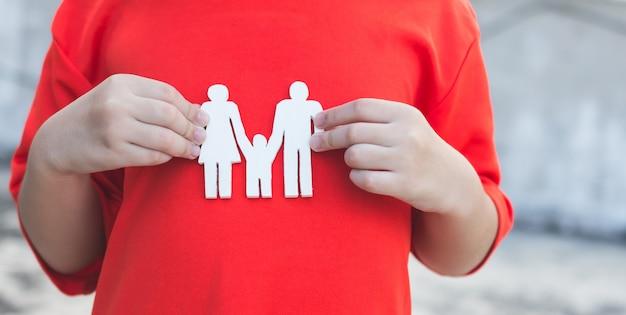Kinderhände, die kleine vorbildliche familie, konzeptfamilie halten