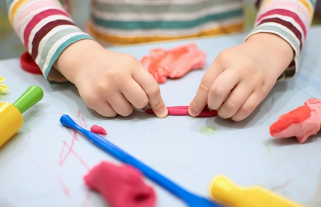 Kinderhände, die mit buntem ton spielen plastilin. knete, soziale distanz quarantäne covid-19, selbstisolation, online-bildungskonzept, homeschooling. kleinkindmädchen zu hause, kindergarten geschlossen.