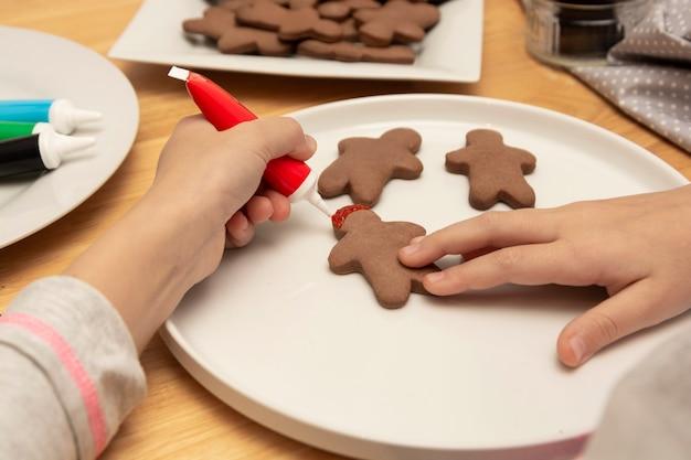 Kinderhände, die plätzchen eines weihnachtslebkuchens unter verwendung des farbigen glazeon, holztisch, draufsicht verzieren. weihnachtsplätzchen.