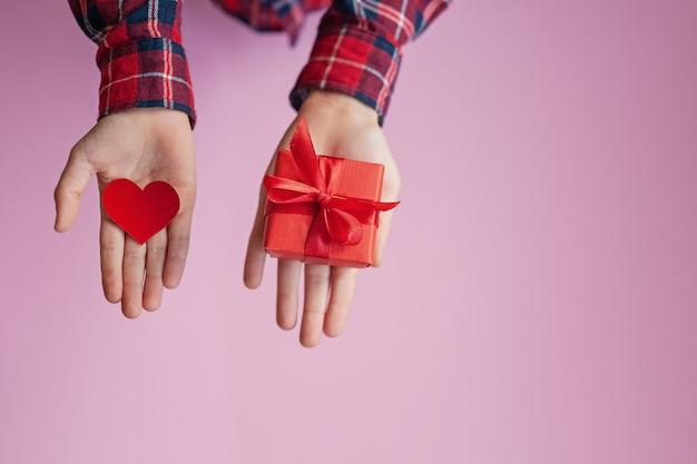 Kinderhände, die rotes papierherz und kasten anwesend in den händen halten. valentinstag-konzept.