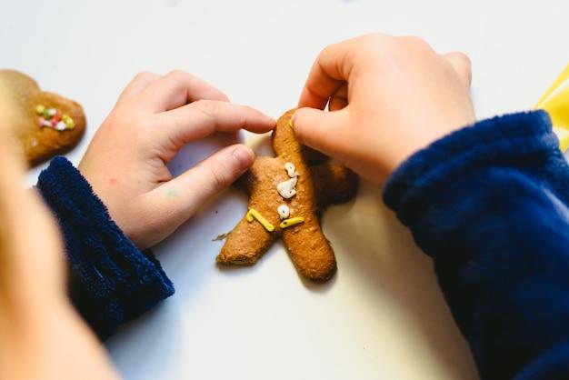 Kinderhände, die selbst gemachte lebkuchenplätzchen mit bunten dekorationen vorbereiten.