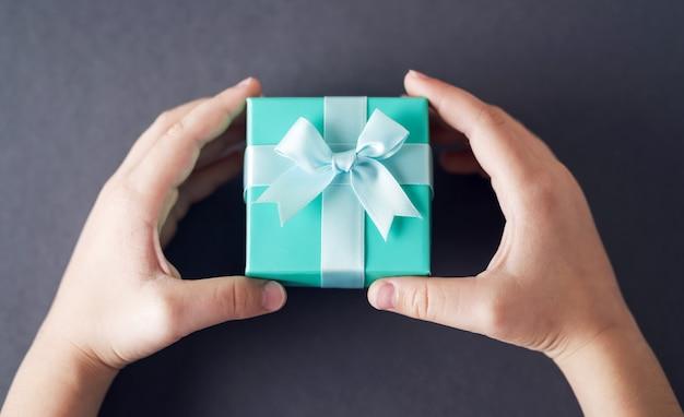 Kinderhände, die türkisfarbene geschenkbox auf grau halten