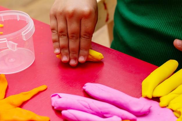 Kinderhände formen bunte teignahaufnahme. konzept der kindererziehung