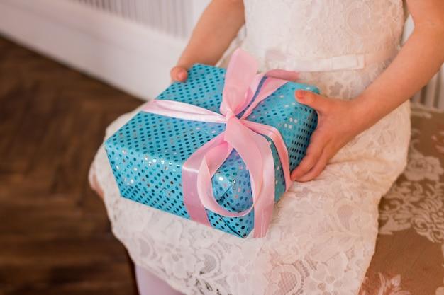 Kinderhände halten einen blauen geschenkkarton mit rosa schleife