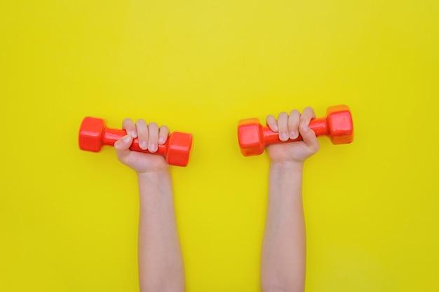 Kinderhände halten rote hanteln. das konzept von sport und einem gesunden lebensstil.
