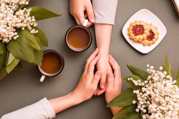 Kinderhände halten tassen tee und einander. treffen und teetrinken. ansicht von oben