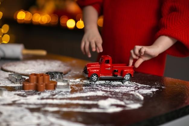 Kinderhände im roten winterpullover, der mit weihnachtsspielzeugauto auf einem tisch mit mehl spielt