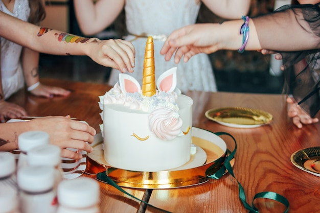 Kinderhände, kleine mädchen greifen nach dem kuchen. großes schönes kucheneinhorn auf dem geburtstag kleiner prinzessin auf festlicher tabelle