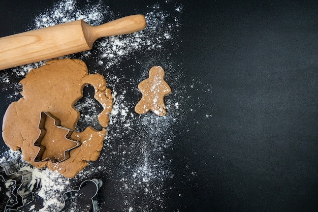 Kinderhände machen neujahrs-lebkuchen auf einem holztisch. kekse mit einem ausstecher backen. neujahrs- und weihnachtskonzept.